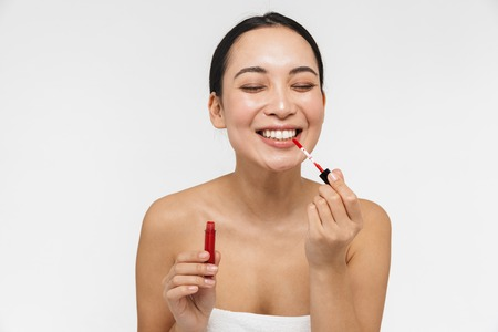Photo of a beautiful young pretty asian woman with healthy skin posing naked isolated over white wall background holding lipstick. Reklamní fotografie