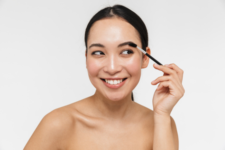 Photo of a beautiful young pretty asian woman with healthy skin posing naked isolated over white wall background holding brow styler. Stock Photo