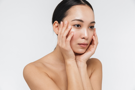 Image of a beautiful young pretty asian woman with healthy skin posing naked isolated over white wall background. Stock Photo
