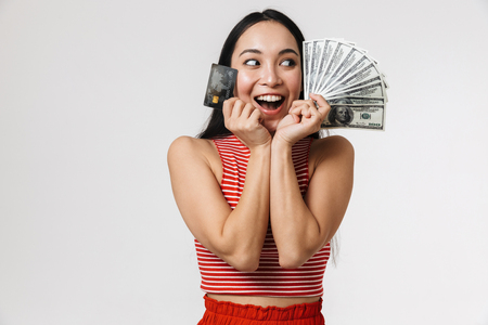 Photo of a beautiful young pretty asian excited woman posing isolated over white wall background holding credit card and money.