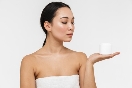Photo of a beautiful young pretty asian woman with healthy skin posing naked isolated over white wall background holding cream.
