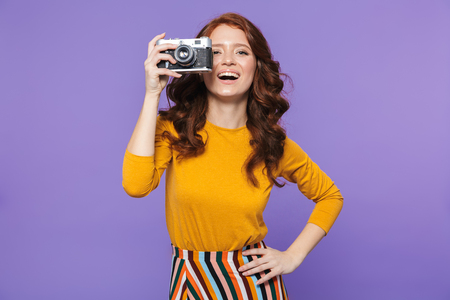 Photo of happy redhead woman wearing yellow clothes holding retro vintage camera and taking picture isolated over purple background