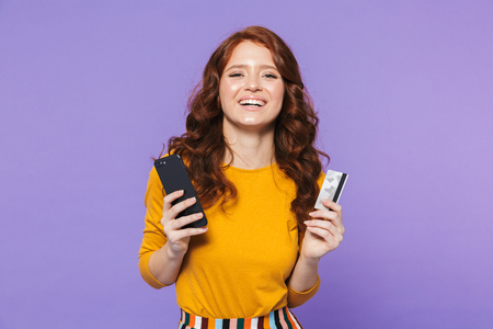 Portrait of a pretty cheerful young redheaded woman standing isolated over violet background, using mobile phone, showing credit card Stockfoto