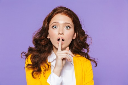 Portrait of a pretty young redheaded woman standing isolated over violet background, showing silence gesture