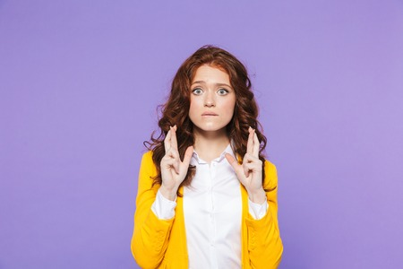 Portrait of a pretty worried young redheaded woman standing isolated over violet background 写真素材