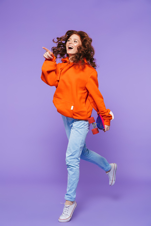 Full length portrait of a pretty young redheaded woman jumping isolated over violet background, holding skateboard Stok Fotoğraf