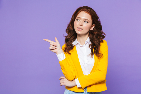 Image of caucasian redhead woman wearing yellow jacket smiling and pointing finger aside isolated over purple background