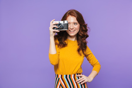 Photo of cheery redhead woman wearing yellow clothes holding retro vintage camera and taking picture isolated over purple background