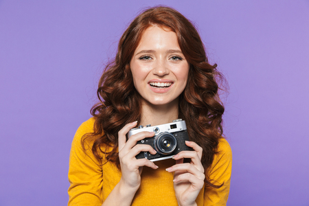 Photo of european redhead woman wearing yellow clothes holding retro vintage camera and taking picture isolated over purple background Stock Photo