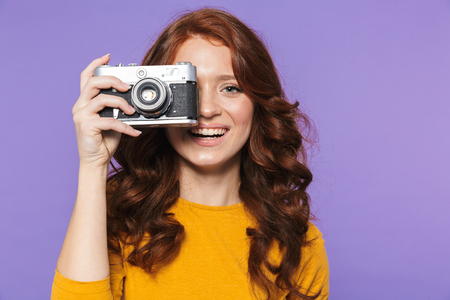 Photo of adorable redhead woman wearing yellow clothes holding retro vintage camera and taking picture isolated over purple background
