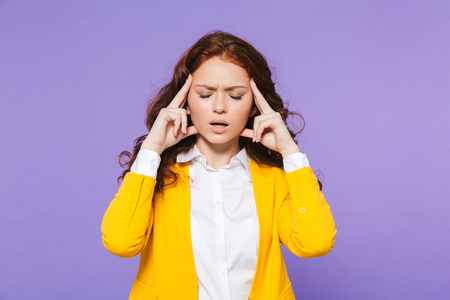 Portrait of a pretty upset young redheaded woman standing isolated over violet background, having a headache