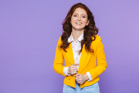 Image of charming redhead woman wearing yellow jacket smiling and looking at camera isolated over purple background