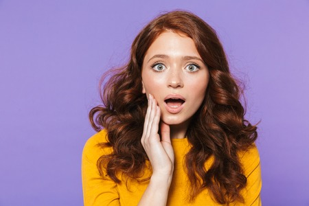Portrait of a pretty excited young redheaded woman standing isolated over violet background