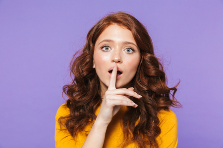 Photo of beautiful redhead woman wearing yellow clothes holding finger at her lips and asking to keep secret isolated over purple background