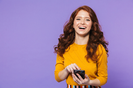 Portrait of a pretty young redheaded woman standing isolated over violet background, using mobile phone, pointing