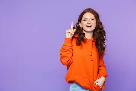 Portrait of a pretty young redheaded woman standing isolated over violet background, pointing finger at copy space