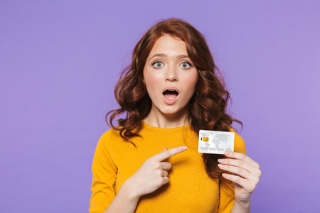 Portrait of a pretty excited young redheaded woman standing isolated over violet background, showing plastic credit card