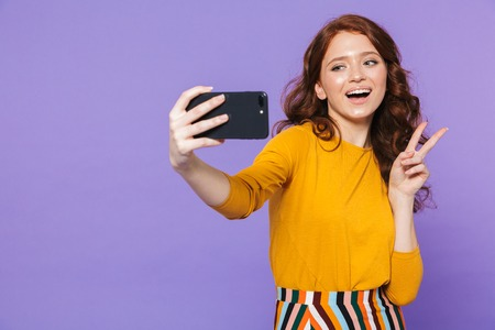 Portrait of a pretty young redheaded woman standing isolated over violet background, taking a selfie, peace Reklamní fotografie