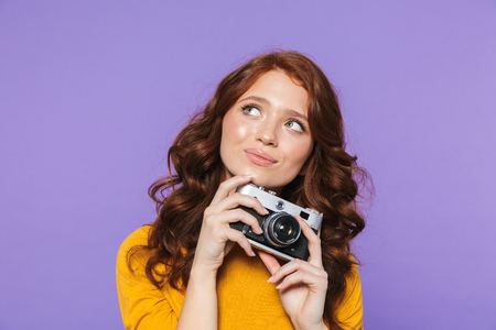 Photo of alluring redhead woman wearing yellow clothes holding retro vintage camera and taking picture isolated over purple background