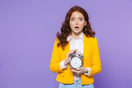 Portrait of a pretty upset young redheaded woman standing isolated over violet background, holding alarm clock