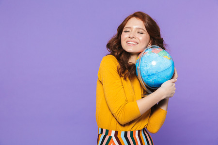 Photo of alluring redhead woman wearing yellow clothes smiling and holding earth globe isolated over purple background Foto de archivo