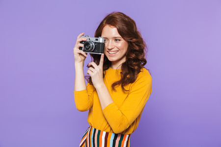 Photo of stylish redhead woman wearing yellow clothes holding retro vintage camera and taking picture isolated over purple background