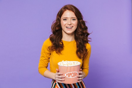 Portrait of a pretty cheerful young redheaded woman standing isolated over violet background, eating popcorn