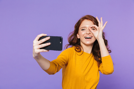 Portrait of a pretty young redheaded woman standing isolated over violet background, taking a selfie, ok