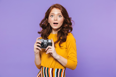 Photo of elegant redhead woman wearing yellow clothes holding retro vintage camera and taking picture isolated over purple background