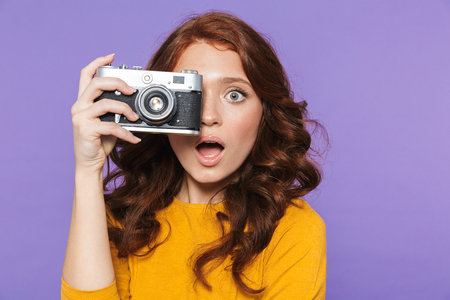 Photo of positive redhead woman wearing yellow clothes holding retro vintage camera and taking picture isolated over purple background