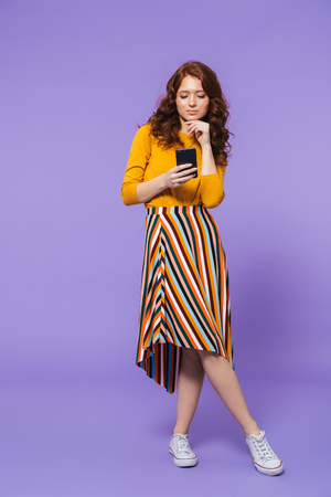 Full length portrait of a pretty young redheaded woman standing isolated over violet background, using mobile phone 版權商用圖片