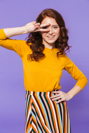 Portrait of a pretty young redheaded woman standing isolated over violet background, posing, gesturing, peace gesture