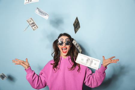 Portrait of rich young woman wearing funny sunglasses laughing while standing under falling dollars money isolated over blue background in studio 스톡 콘텐츠