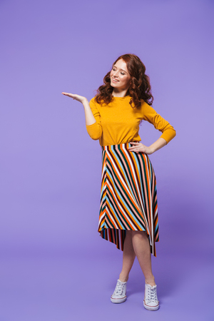 Full length portrait of a pretty young redheaded woman standing isolated over violet background, pointing finger at copy space
