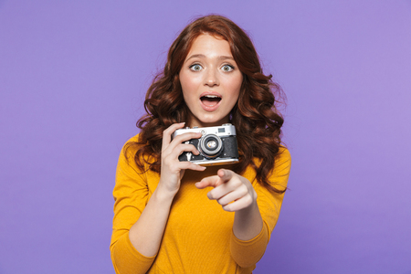 Photo of attractive redhead woman wearing yellow clothes holding retro vintage camera and taking picture isolated over purple background