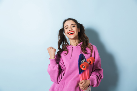 Portrait of a cheerful young girl wearing hoodie standing isolated over blue background, holding skateboard