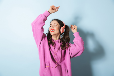 Portrait of a cheerful young girl wearing hoodie standing isolated over blue background, wearing headphones