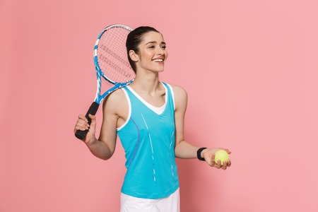 Image of happy excited amazing beautiful young pretty fitness woman holding tennis racket posing isolated over pink wall background. Stock Photo