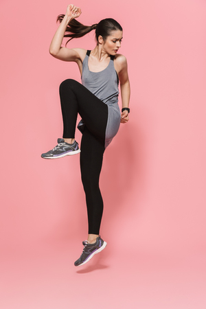 Image of concentrated amazing beautiful young pretty fitness woman running make sport exercises isolated over pink wall background. Stock Photo