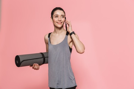 Image of amazing beautiful young pretty fitness woman talking by mobile phone holding rug isolated over pink wall background. Reklamní fotografie