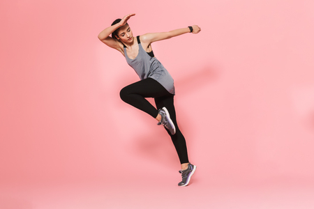 Image of concentrated amazing beautiful young pretty fitness woman running make sport exercises isolated over pink wall background. Reklamní fotografie