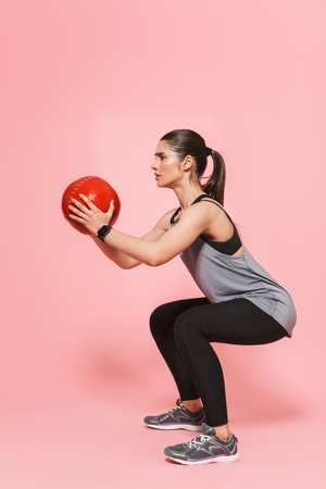 Image of amazing beautiful young pretty fitness woman make sport exercises with ball isolated over pink wall background. Stock Photo - 125292245
