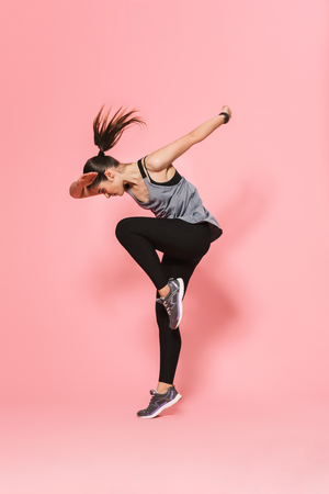 Image of beautiful young pretty fitness woman running make sport exercises isolated over pink wall background. Reklamní fotografie