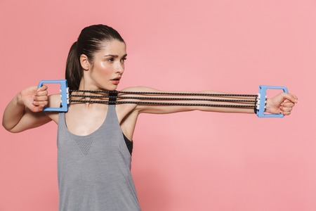 Image of amazing beautiful young pretty fitness woman make sport exercises with equipment isolated over pink wall background.
