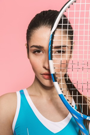 Image of amazing beautiful young pretty fitness woman holding tennis racket posing isolated over pink wall background.