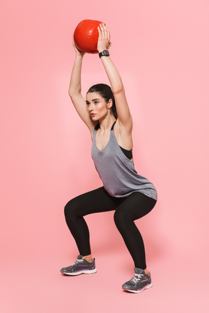 Image of amazing beautiful young pretty fitness woman make sport exercises with ball isolated over pink wall background. Reklamní fotografie