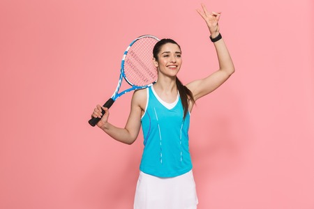 Image of happy excited amazing beautiful young pretty fitness woman holding tennis racket posing isolated over pink wall background. Reklamní fotografie
