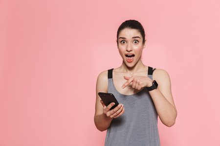 Image of amazing surprised beautiful young pretty fitness woman using mobile phone isolated over pink wall background.