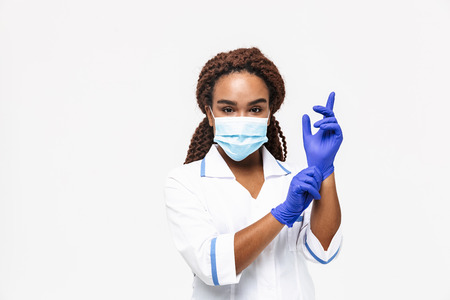 Image of african american nurse or doctor woman wearing medical face mask wearing disposable gloves isolated against white background