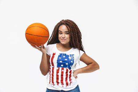 Portrait of brunette african american woman rejoicing and holding basketball during game while standing isolated against white wall